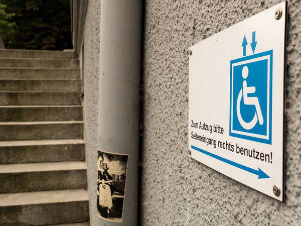 Hinweisschild für RollstuhlfahrerInnen am Nachbarschaftshaus Urbanstrasse